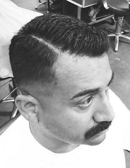 Una foto de la barbería de un hombre con bigote y con el lado cortado parte del pelo con un corte de pelo contorno ejecutivo
