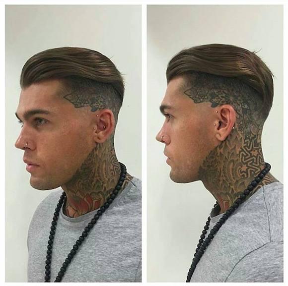 Una imagen de la barbería de un individuo con un corte de pelo corte sesgado y peinado hacia atrás el pelo que cubre sus tatuajes