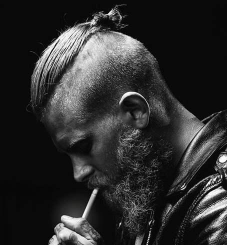 Una fotografía de un hombre inconformista con un peinado hombre bollo corte sesgado y la barba
