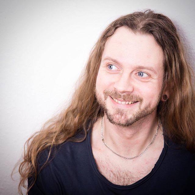 Una fotografía de un hombre rubio alemán con su largo cabello ondulado en un corte de pelo hasta los hombros Más allá después de conseguir un corte de pelo en capas