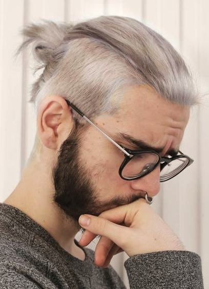 Una imagen de un hombre con un peinado Undercut gran hombre moño y una última moda la barba