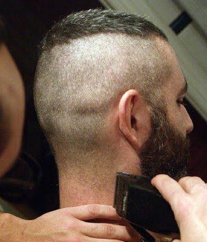 Una imagen de la barbería de un caballero barbudo conseguir un corte de pelo alto y estrecho agudo