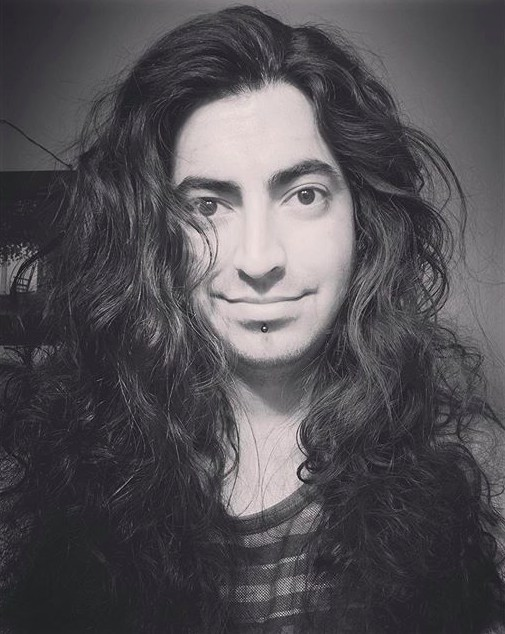 Una fotografía de un hombre barbudo hermoso con un peinado más allá, a la espalda de su largo pelo rizado