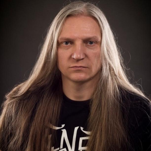 Una fotografía de un varón blanco con el pelo largo de color gris labrado hacia abajo y se enderezó con una plancha