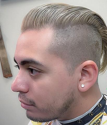 Una imagen de un varón joven rubia con un corto peinado hacia atrás rebajada combinada con la pomada