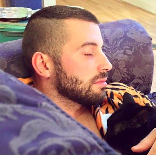 Una imagen de un hombre con un corte de pelo alto y apretado fresco y una barba inconformista que duerme en el sofá